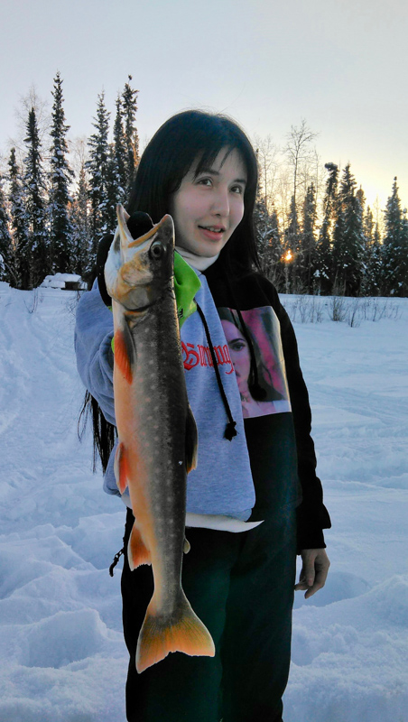 Woman Holding Up the Fish She Caught While Ice Fishing in Alaska
