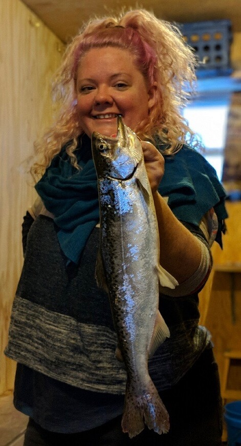 Woman Holding Up the Fish She Caught On Her Adventure