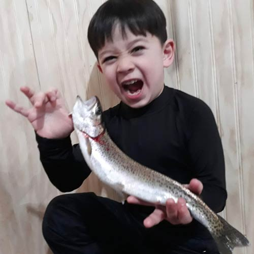 Young Boy Holding the Fish He Caught Ice Fishing in Alaska